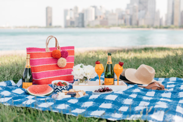 Bows & Sequins hosting a picnic along Lake Michigan with a striped tote and Veuve Clicquot champagne.