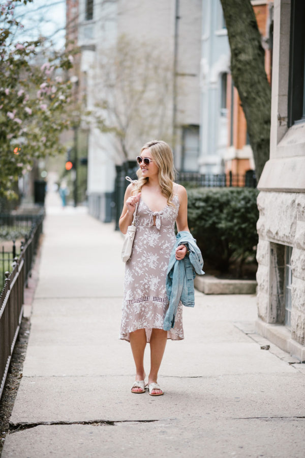 Fashion blogger Bows & Sequins wearing an ASTR tie-front floral midi dress with Call It Spring sunglasses, Soludos knotted slides, and a Clare V Petit Henri bag.