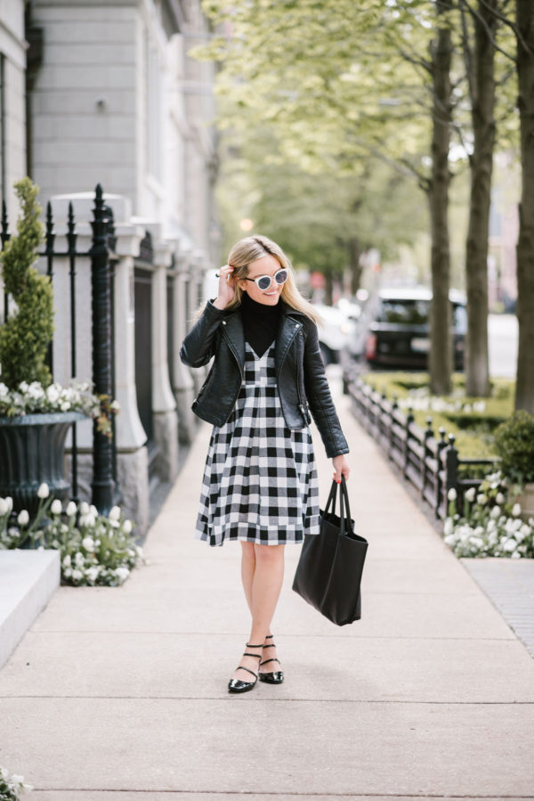 Lifestyle blogger Bows & Sequins wearing a Modcloth gingham midi dress with a moto jacket, leather tote, and Nordstrom black & white sunglasses.