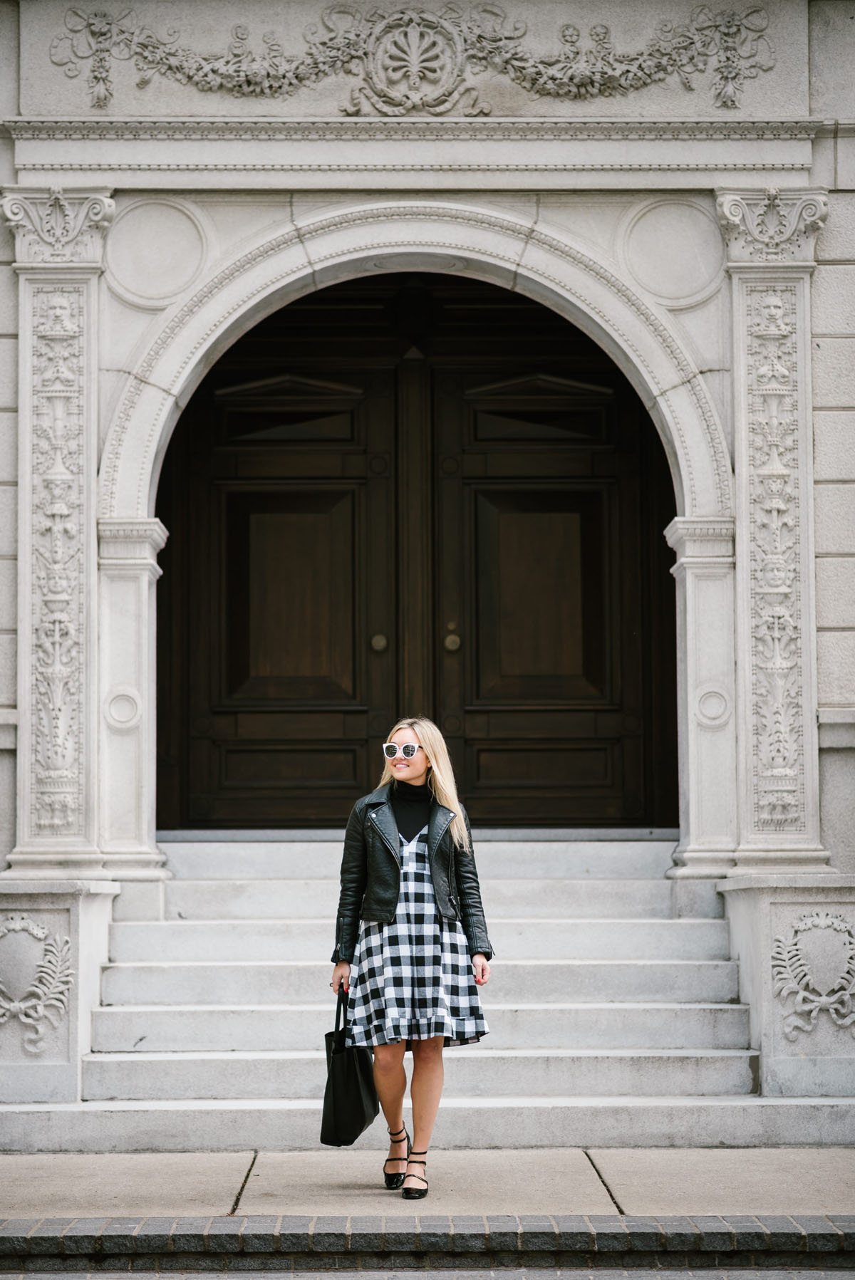 Bows & Sequins wearing a Topshop moto jacket and black gingham Modcloth midi dress with a leather tote and strappy Mary Janes.