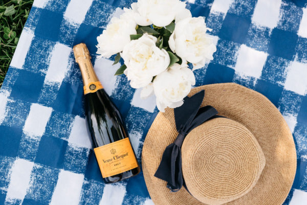Tuckernuck straw hat with a navy hat on a Crate & Barrel blue gingham picnic blanket and Veuve Clicquot champagne.