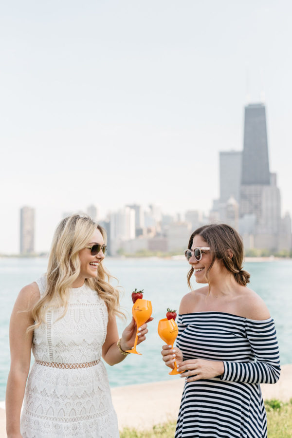 Chicago lifestyle bloggers Bows & Sequins and Hallie Wilson drinking Veuve Clicquot champagne by Lake Michigan.
