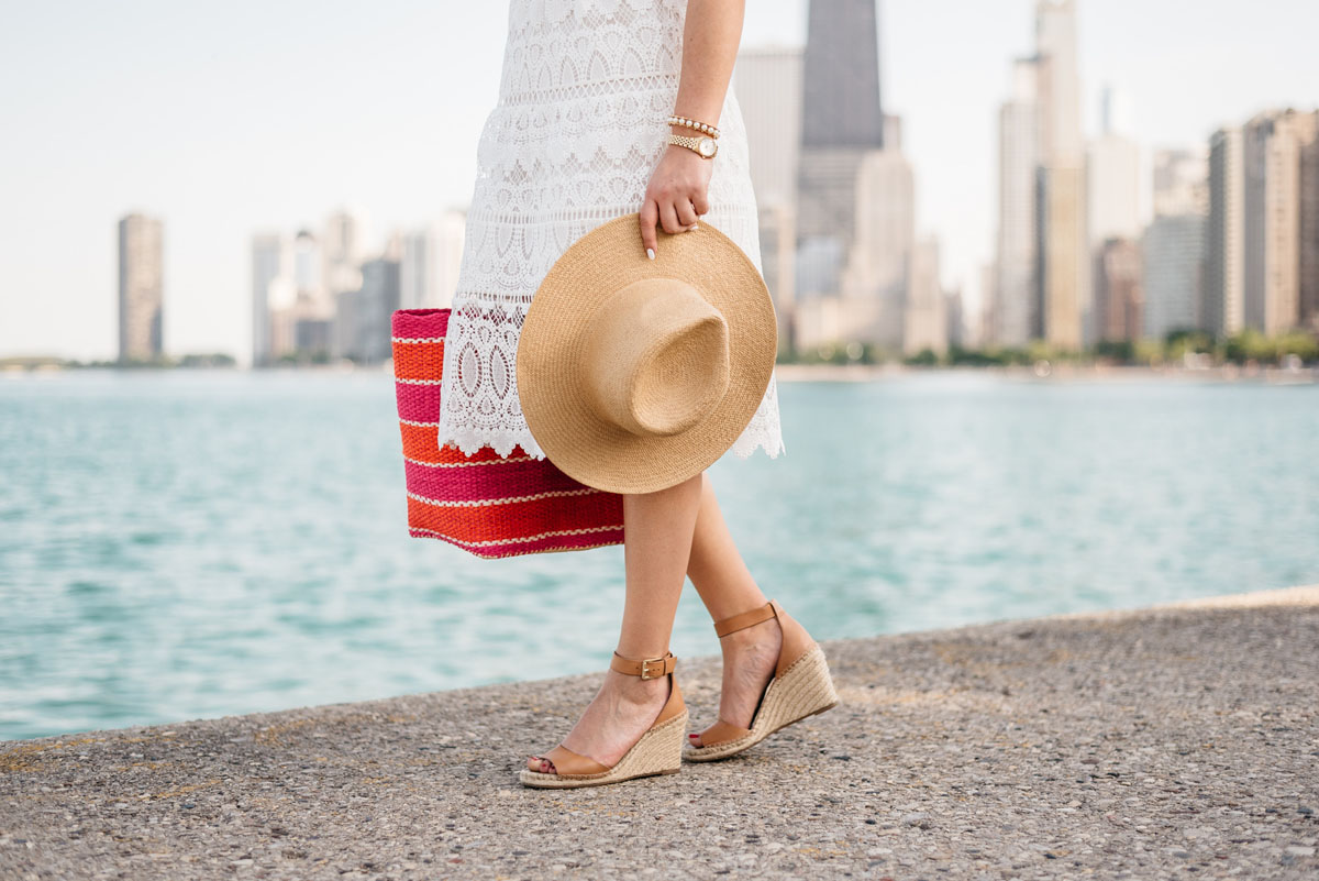Fashion blogger Jessica Sturdy of Bows & Sequins wearing a J.O.A. lace dress and Vince Camuto espadrille wedges with a striped straw tote and an Old Navy hat.