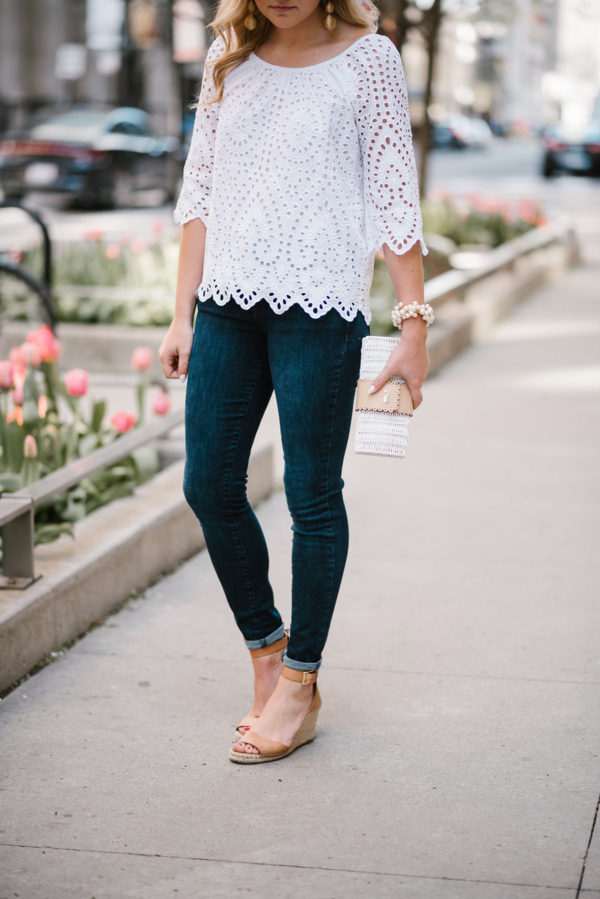 Chicago fashion blogger Bows & Sequins wearing an eyelet top by Vineyard Vines with Old Navy jeans with a white wicker clutch and a Sweet & Spark pearl bracelet.