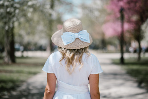 Bows & Sequins wearing a straw sunhat with a seersucker bow paired with a little white dress for the Kentucky Derby.