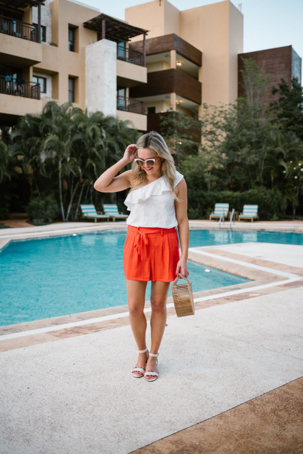 Travel and lifestyle blogger Bows & Sequins wearing a white Old Navy ruffle top with orange tie-waist shorts and a Cult Gaia Ark bamboo handbag.