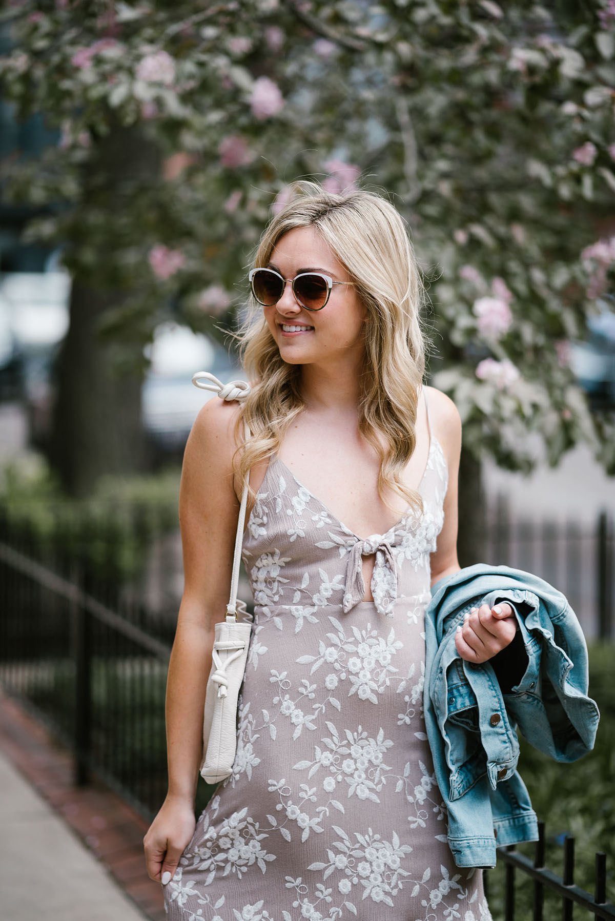 Jessica of Bows & Sequins wearing a tie-front floral midi dress, Call It Spring white frame sunglasses, and a Clare V bag with a Gap jean jacket.