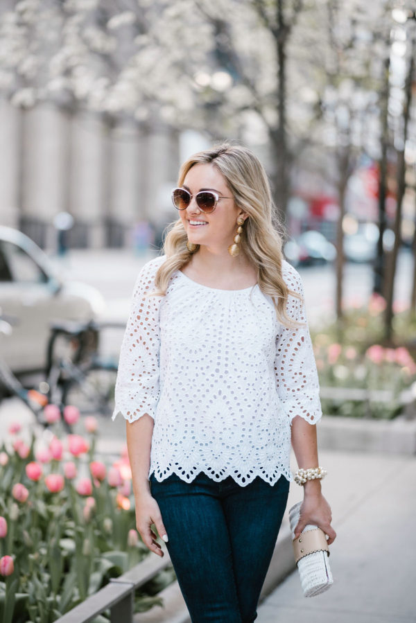 Bows & Sequins wearing a white Vineyard Vines eyelet top with Call It Spring white rim sunglasses, Tuckernuck gold statement earrings, and a wicker rattan clutch in downtown Chicago.