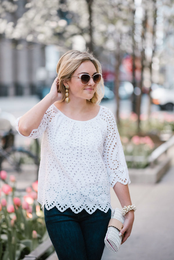 Chicago blogger Jessica Sturdy styling a white eyelet top with white rim sunglasses and gold statement earrings in downtown Chicago.
