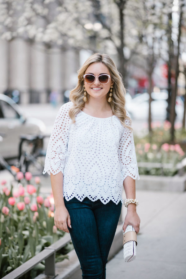 Lifestyle blogger Bows & Sequins styling a white Vineyard Vines eyelet top with Old Navy jeans, Call It Spring sunglasses, a Sweet & Spark pearl bracelet, and gold drop statement earrings.