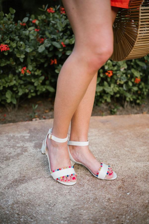 Travel blogger Bows & Sequins wearing J.Crew pom pom sandals.