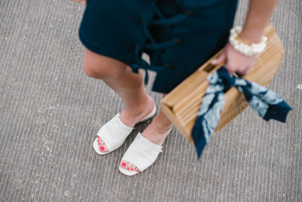 Chicago fashion blogger Bows & Sequins wearing white Kurt Geiger slides with a Cult Gaia bamboo bag, a navy bandana, and a pearl bracelet.