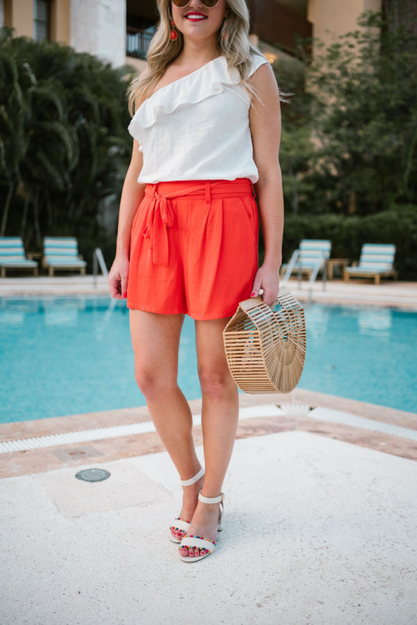 Chicago-based travel blogger Bows & Sequins wearing orange tie-waist shorts from Old Navy and J.Crew pom pom sandals with a Cult Gaia bamboo bag at the Fairmont Mayakoba in Mexico.