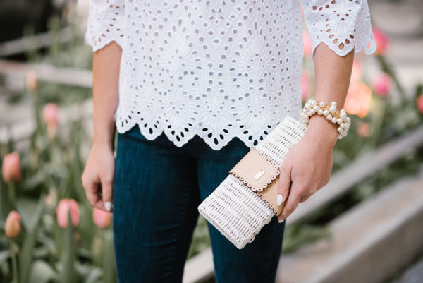 Fashion blogger Bows & Sequins holding a Vineyard Vines white wicker rattan clutch and wearing a Sweet & Spark pearl bracelet.