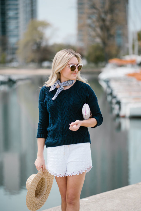 Lifestyle blogger Bows & Sequins wearing Nordstrom sunglasses, a blue bandana, a navy summer sweater, and white eyelet shorts.