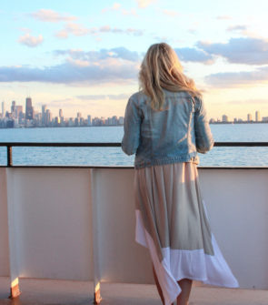 Chicago fashion blogger Bows & Sequins on a boat on Lake Michigan with the Chicago skyline in the background at sunset.