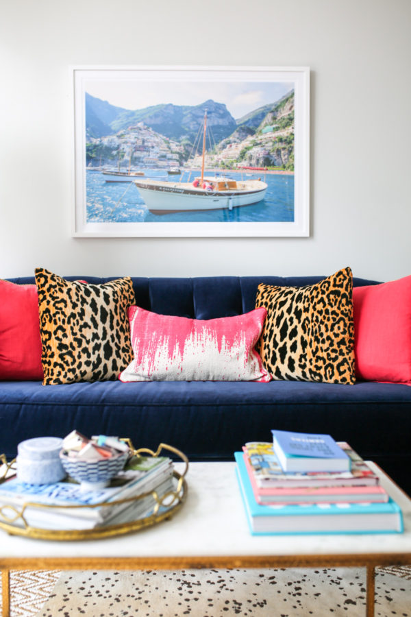 Bows & Sequins living room decor: Gray Malin Italy print, pink and leopard throw pillows, navy velvet couch, stacked coffee table books.