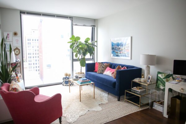 Bows & Sequins Chicago living room decor with a fiddle leaf fig, Gray Malin print, custom velvet navy couch, pink wingback chair, and layered area rugs