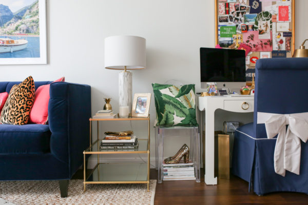 Bows & Sequins Chicago living room office with a navy velvet couch, mirror end table with stacked coffee books, navy bow chair