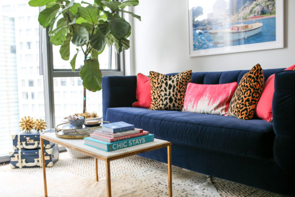 Chicago living room decor with Gray Malin Italy print, navy velvet couch, pink and leopard pillows, and marble lamp.