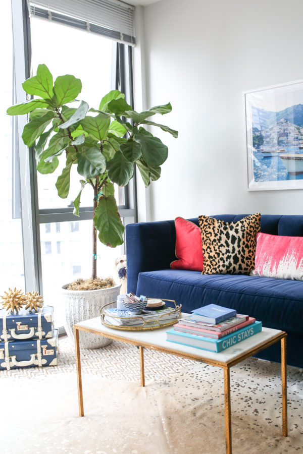 Bows & Sequins living room decor with a gold and white marble coffee table, Society Social navy velvet couch, pink and leopard throw pillows.