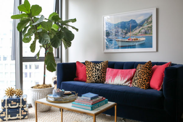 Bows & Sequins living room decor with a fiddle leaf fig, stacked trunks, Gray Malin print, Society Social velvet couch, pink and leopard throw pillows