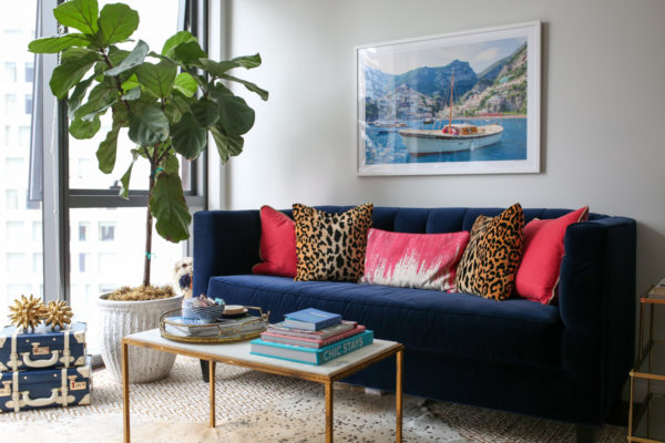 Bows & Sequins living room decor with a fiddle leaf fig, stacked trunks, Gray Malin print, Society Social velvet couch, and pink and leopard throw pillows.