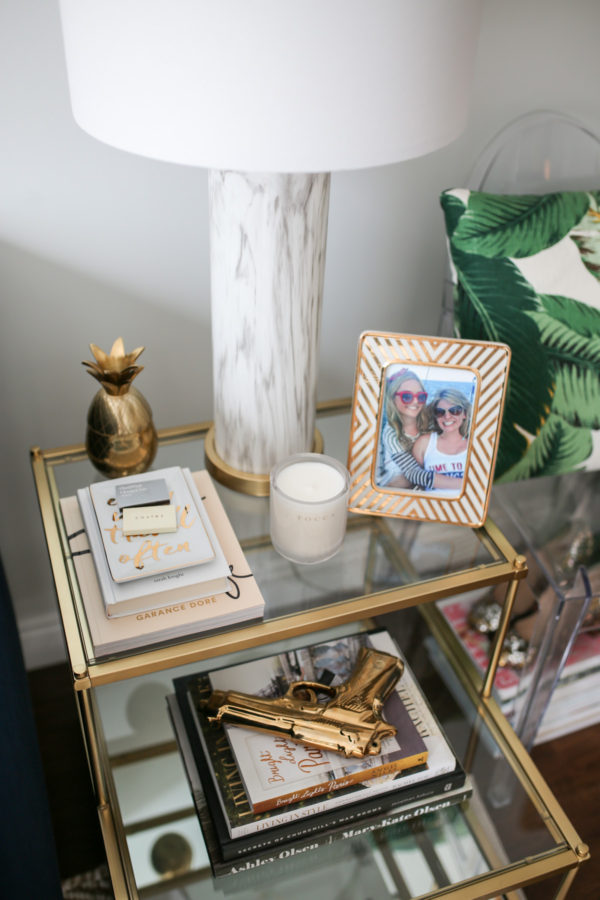 Chicago blogger living room decor with a gold glass end table, marble lamp, and gold pineapple decor.