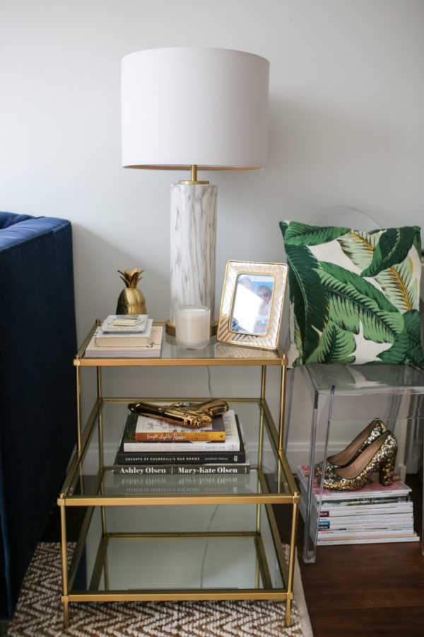 Chicago blogger living room decor with a gold glass end table, marble lamp, palm printed pillow, and gold pineapple decor.