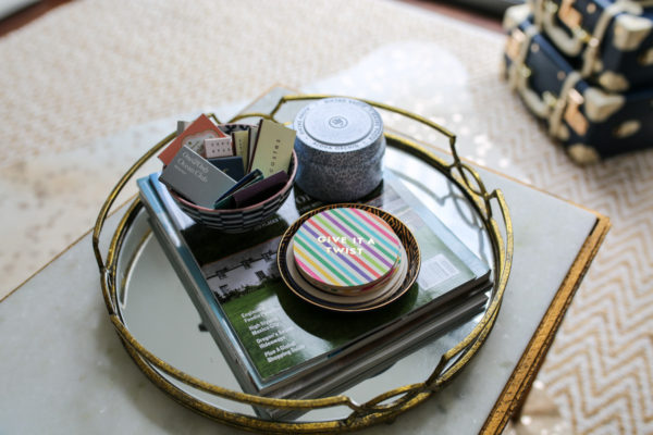 Bows & Sequins coffee table decor with a gold mirror tray with drink accessories.
