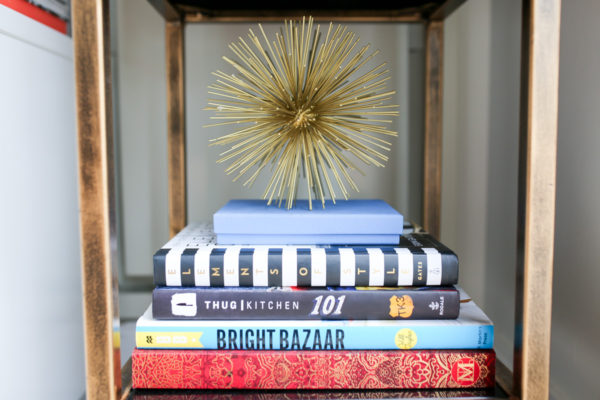 Bows & Sequins bookshelf decor with stacked Elements of Style, Thug Kitchen cook book, Bright Bazaar coffee table book, and decorative spike sphere.