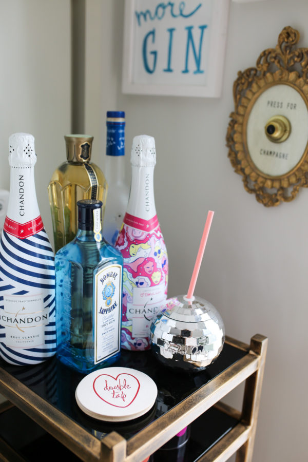 Bows & Sequins shares her bar cart: Chandon sparkling wine, Moët, disco ball mug, and Double Tap heart coasters.