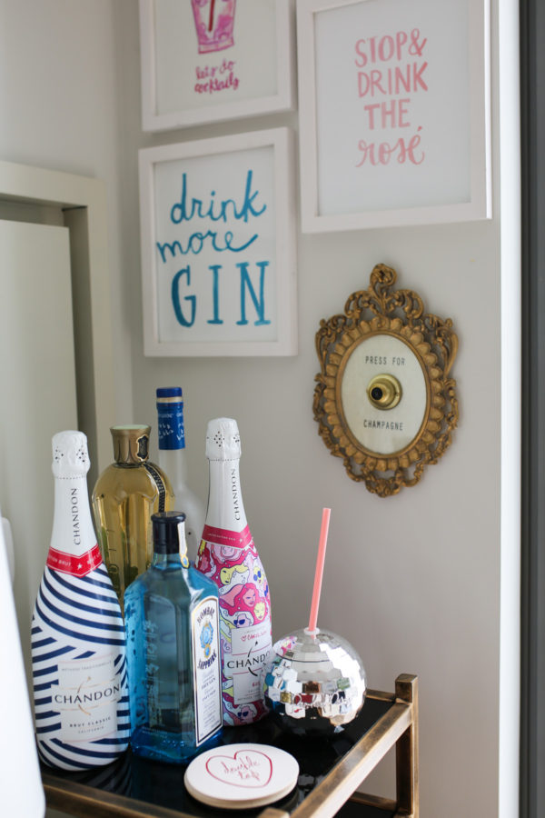 Bows & Sequins shares her bar cart: Chandon sparkling wine, Moët, disco ball mug, and Drink More Gin wall print.