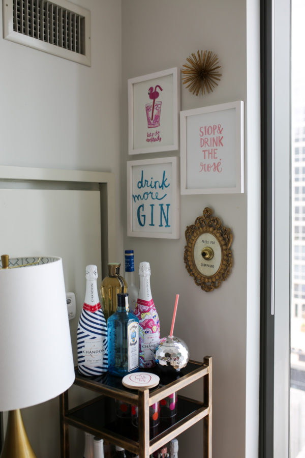 Bows & Sequins shares her bar cart: Chandon sparkling wine, Moët, disco ball mug, Drink More Gin and Stop and Drink the Rosé wall prints.