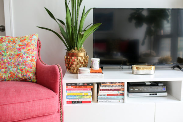 Bows & Sequins Chicago living room decor with a pink wingback chair and colorful printed throw pillow, snake plant, and stacked books.