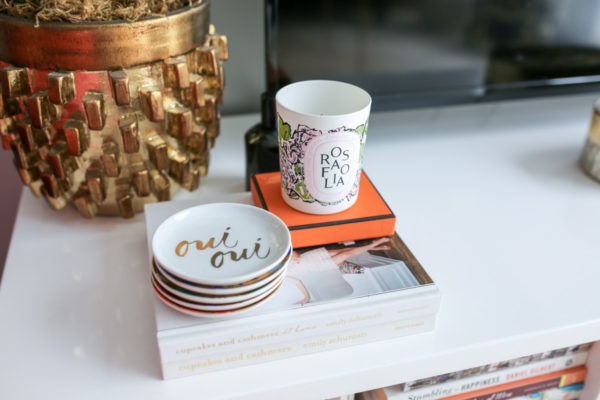 Bows & Sequins shares her living room decor in Chicago: oui oui stacked plates, diptyque Rosafolia candle, and cupcakes & cashmere stacked books.