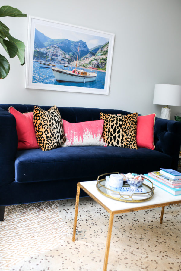 Bows & Sequins navy velvet Society Social couch with pink and leopard throw pillows, framed Gray Malin Italy print, and gold and marble coffee table with mirror tray.