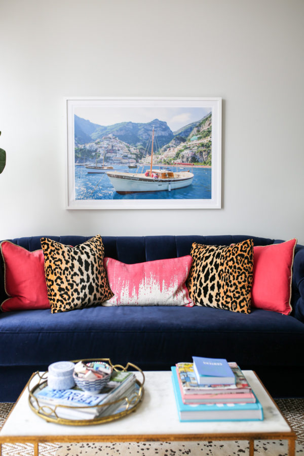 Bows & Sequins navy velvet Society Social couch with pink and leopard throw pillows, framed Gray Malin Italy print, and gold and marble coffee table with mirror tray and stacked books.
