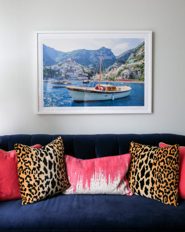 Bows & Sequins Chicago living room with navy velvet Society Social couch with pink and leopard throw pillows and a framed Gray Malin Italy print.