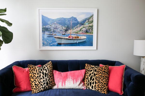 Bows & Sequins Chicago living room with navy velvet Society Social couch with pink and leopard throw pillows, a framed Gray Malin Italy print, fiddle leaf fig, and marble table lamp.