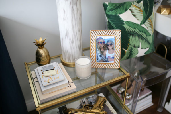 Bows & Sequins living room decor: gold pineapple, palm printed throw pillow, marble lamp, Garance Doré photography book.