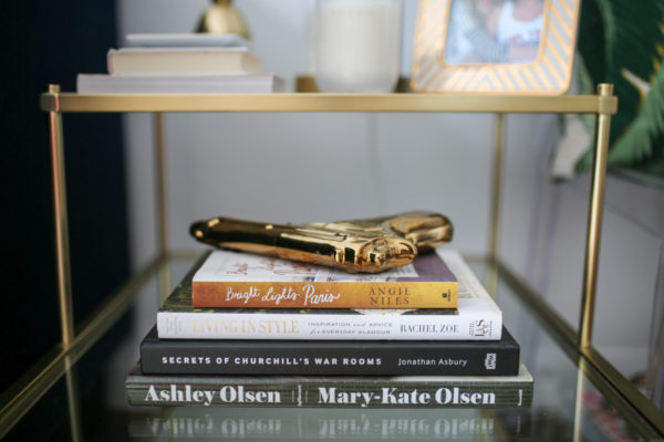 Bows & Sequins living room bookshelf arrangement: Influence by Mary Kate and Ashley Olsen, Living in Style, Bright Lights Paris, and gold plated gun.