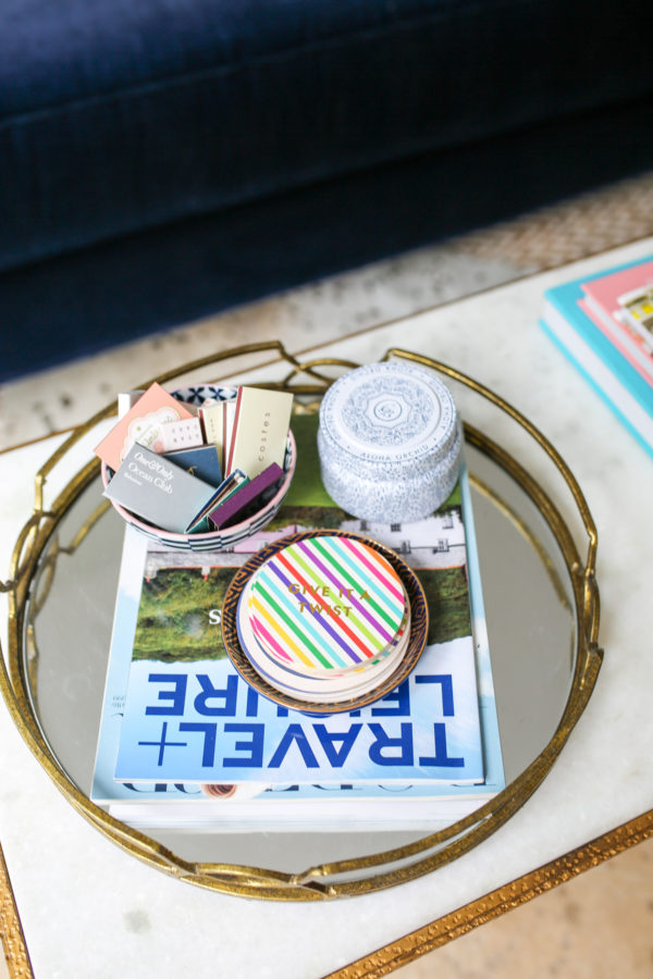 Bows & Sequins living room mirror tray with coasters, matchbox collection, and Travel + Leisure magazine.