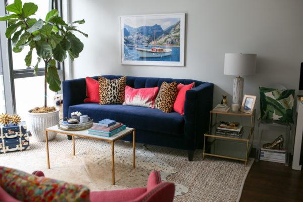 Bows & Sequins Chicago living room decor with a navy blue velvet couch, Gray Malin Italy print, pink and leopard throw pillows, marble coffee table, and layered area rugs.