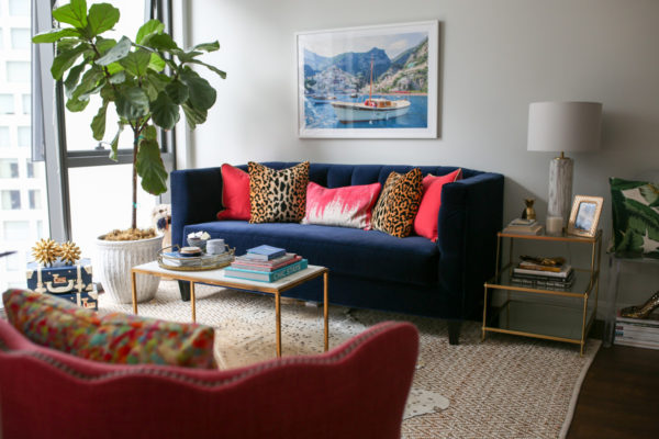 Bows & Sequins Chicago living room decor with a navy blue velvet couch, Gray Malin Italy print, pink and leopard throw pillows, gold and white marble coffee table, and pink wingback chair.