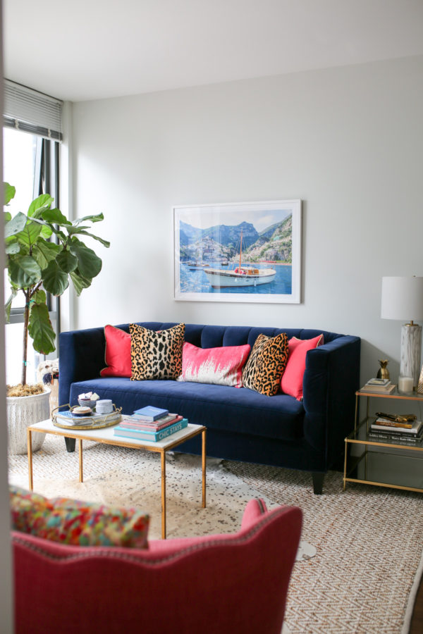 Bows & Sequins Chicago living room decor with a navy blue velvet Society Social couch, Gray Malin Italy print, pink and leopard throw pillows, gold and white marble coffee table, stacked trunks, and pink wingback chair.
