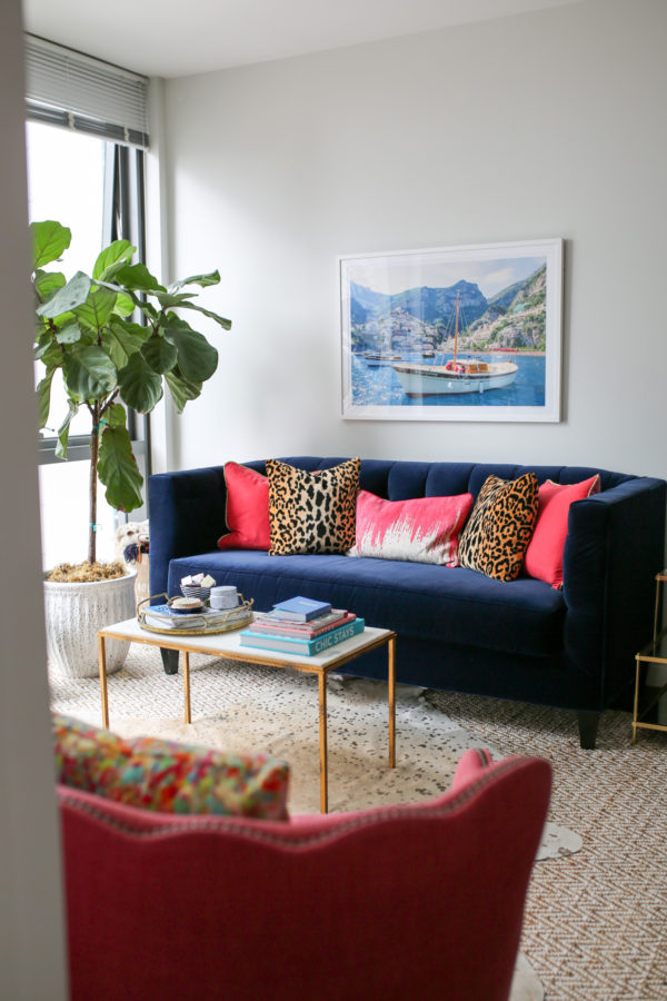 Bows & Sequins Chicago living room decor with a navy blue velvet Society Social couch, Gray Malin Italy print, pink and leopard throw pillows, gold and white marble coffee table, and pink wingback chair.