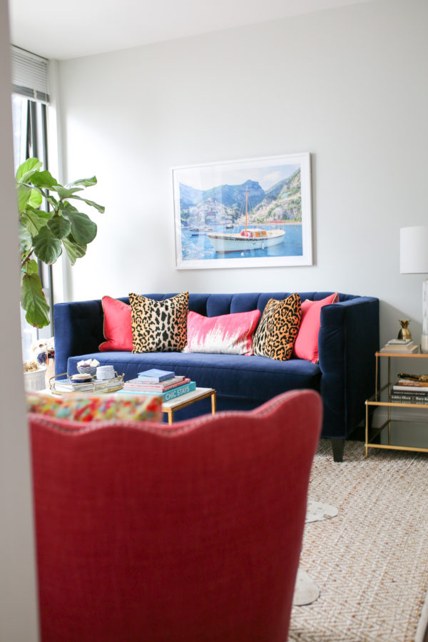 Bows & Sequins Chicago apartment living room with a navy blue velvet Society Social couch, Gray Malin Italy print, pink and leopard throw pillows, gold and white marble coffee table, and pink wingback chair.