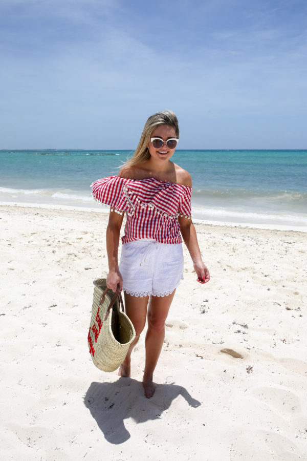 Bows & Sequins, a Chicago-based travel blogger, wearing a red gingham pom pom top with white eyelet shorts in Mexico.