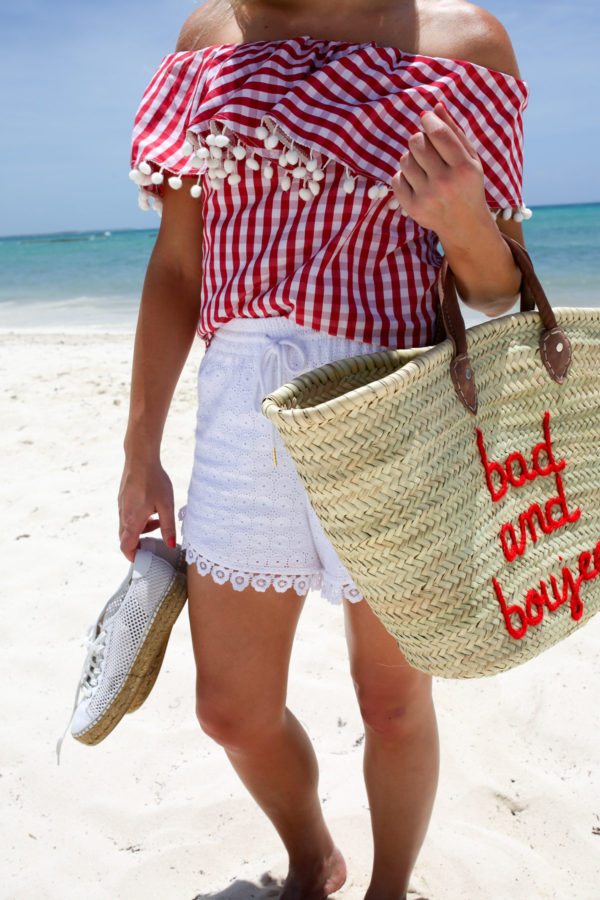 Bows & Sequins wearing white eyelet drawstring shorts with a red gingham top and a Bad and Boujee straw tote on the beach in Mexico.